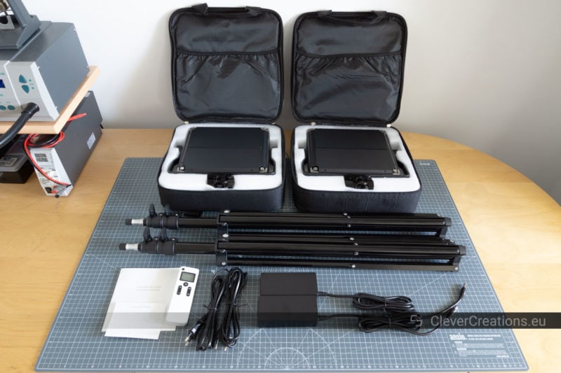 Unboxing of a Neewer 2.4G 660 LED panel kit with two lights, two stands, two power cables and a remote on a desk.