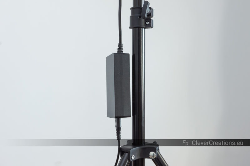 A power adapter dangling next to the pole of a light stand.