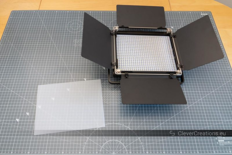 A Neewer 660 LED light with barn doors on a desk with next to it a white diffuser.