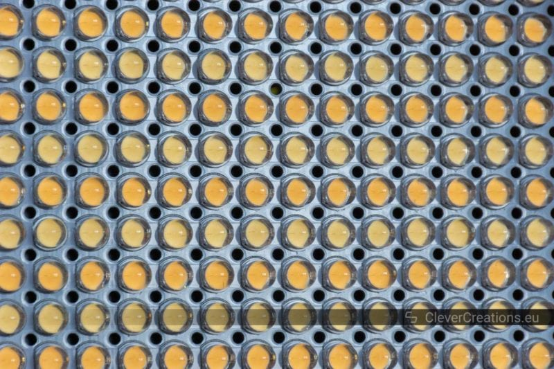 A close-up of rows of white and yellow light emitting diodes on a LED panel.