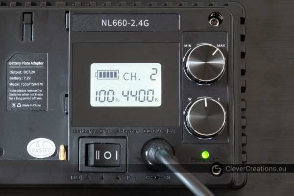A close-up of the LCD screen and control knobs on the rear of a Neewer 660 light.
