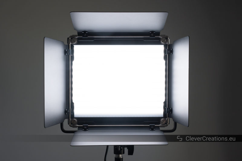 An illuminated Neewer 2.4G 660 LED panel with barndoors viewed from the front.