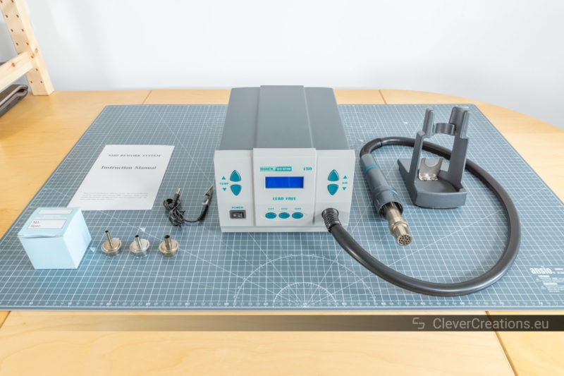 Unboxing of a Quick 861DW hot air rework station with all of its components laid out on a desk.