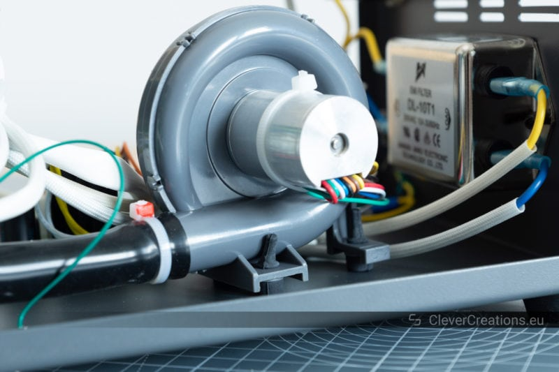 A close-up of an air blower pump mounted on rubber feet to dampen vibration and sound.