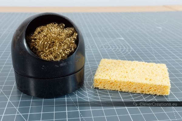 A regular sponge next to a brass sponge for cleaning soldering iron tips.
