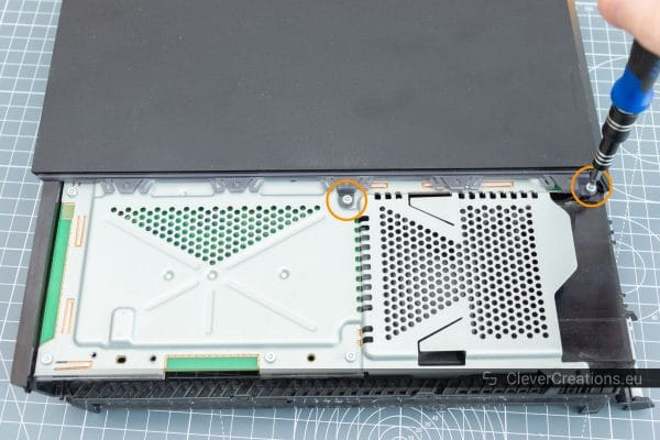 A screwdriver removing torx screws from the plastic cover of a game console.