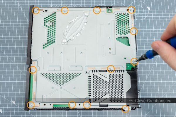 Twelve circled screws on the shielding of a Playstation 4 that need to be removed.