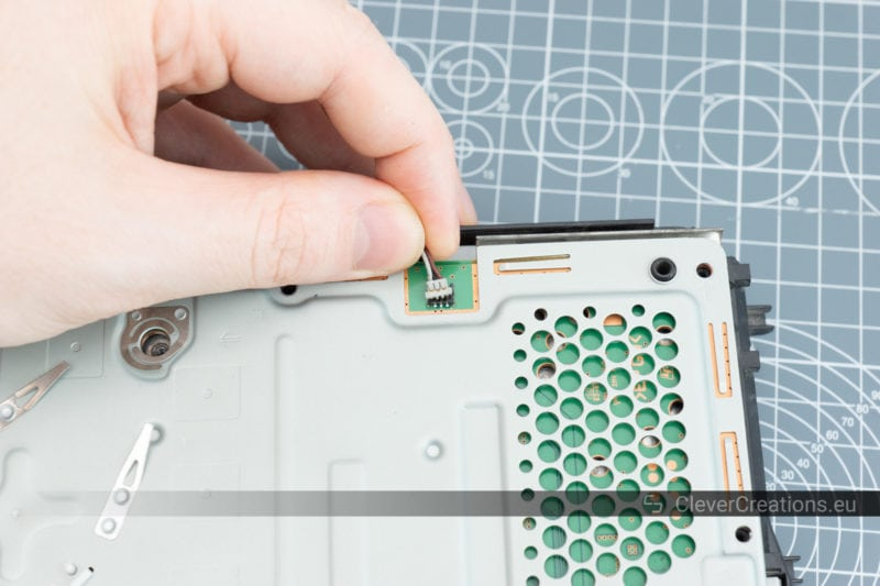 A small connector being removed from the circuit board of a PS4.