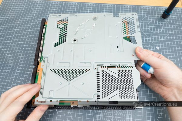 Two hands lifting the shielding of a Playstation 4 out of the console.