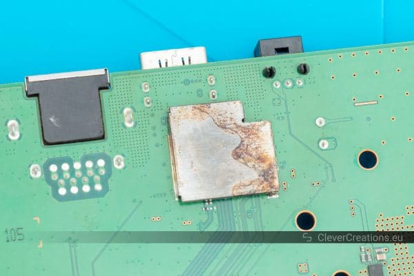 Close-up of corroded shielding on a printed circuit board.