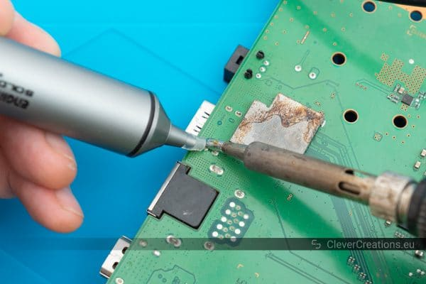 An Engineer SS-02 solder sucker and soldering iron being used to remove solder from a broken HDMI port.