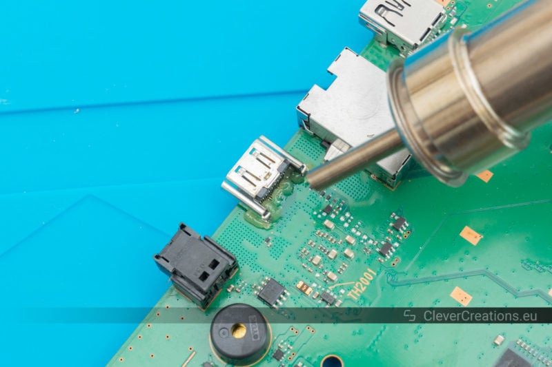 A hot air gun being used to melt flux and solder to repair a PS4 HDMI port.
