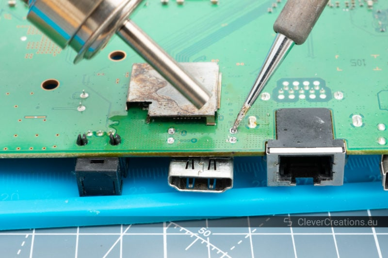 A Quick 861DW hot air gun and soldering iron being used to desolder a HDMI port from a PCB.