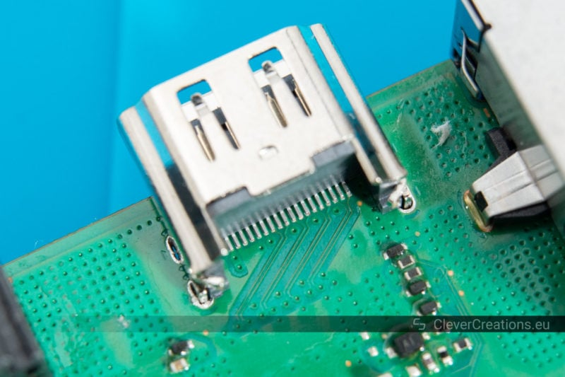 A close-up of a replacement HDMI port placed on a Playstation 4 circuit board.