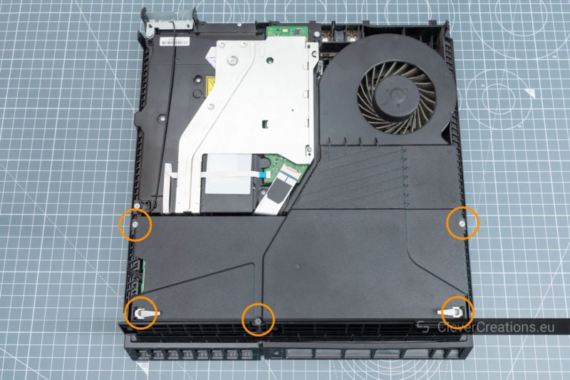 Top view of the inside of a Playstation 4, with circles around the screw that hold the power supply in place.
