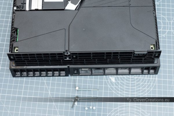 The screws that hold the PS4 power supply in place removed and placed on top of a cutting mat.
