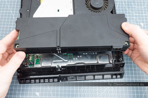 The power supply of a PS4 being lifted out of the console for repair.