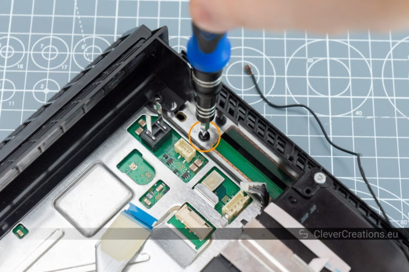 A screwdriver removing a screw from a circuit board.
