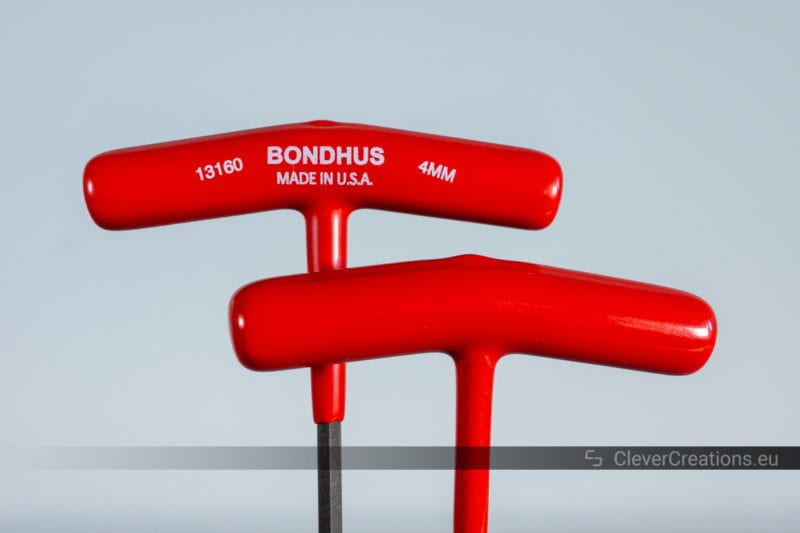 The front and back of two red coated T-handle Allen wrenches.