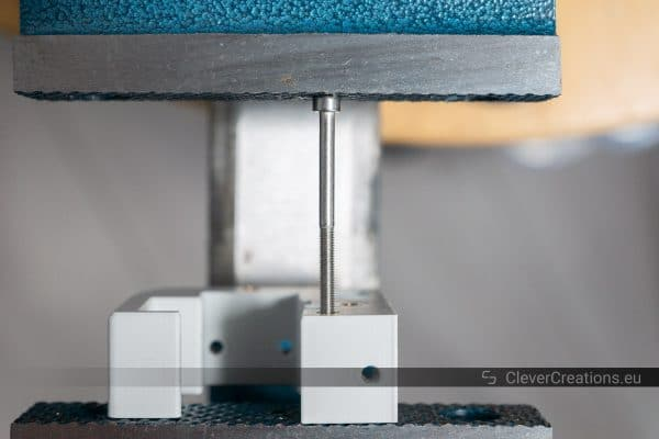 A 3D printed part with stainless steel bolt sticking out, held in place by a vice.
