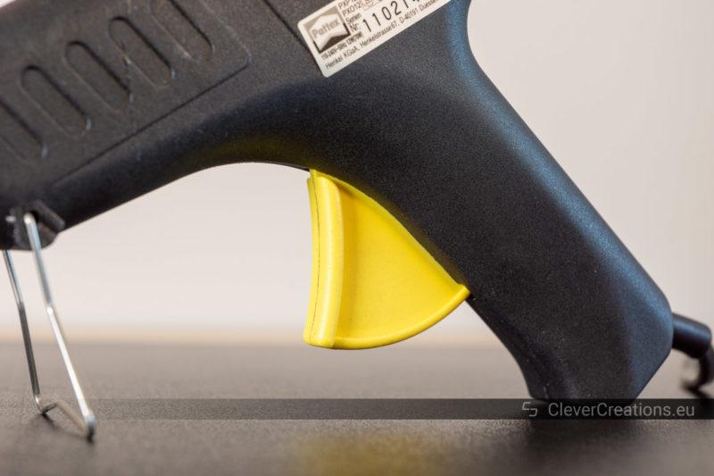 Close-up of a yellow trigger of a hot melt gun.