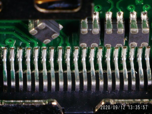 A long row of pins on a PCB, seen at an angle and upside down.