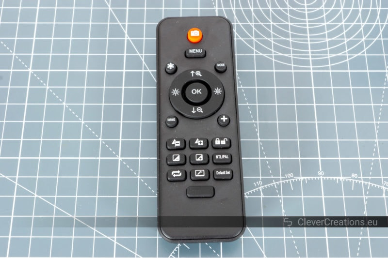 A black remote with a variety of buttons.