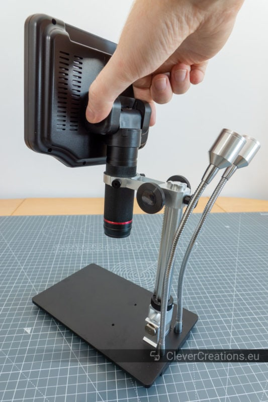 A hand dropping in the objective lens/screen assembly of a digital microscope during installation.