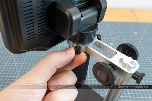 Tightening thumbscrews to clamp the lens on a digital microscope with LCD screen.