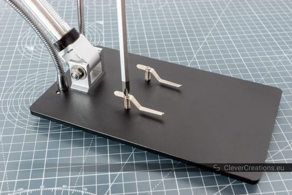 A screwdriver being used to install the PCB holding clamps on a SMD soldering digital microscope.