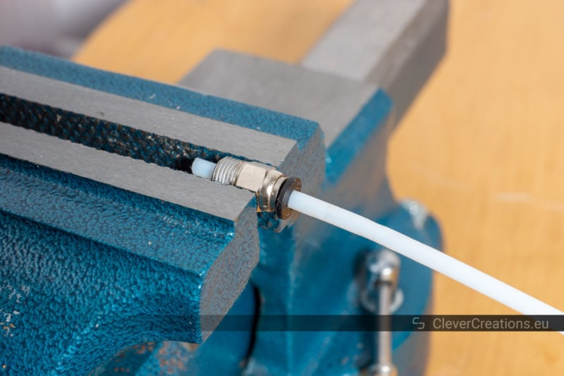 Teflon tubing in a PTC coupling, clamped in a vise.