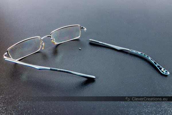 A pair of broken Ray-Ban glasses with a detached loose temple arm.