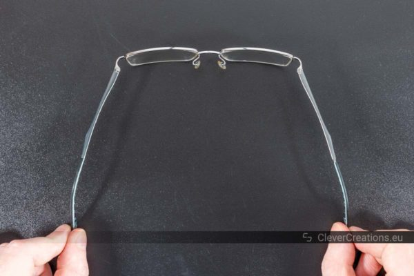 A pair of glasses with spring hinges that extend further than the traditional 90 degrees of barrel hinges.
