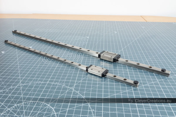 A MGN9 and MGN12 linear guide rail placed next to eachother on a grey cutting mat.