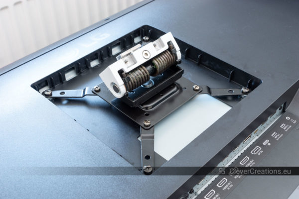 """A VESA 200x200mm mount being installed on the back of a large LG 43"""" screen."""