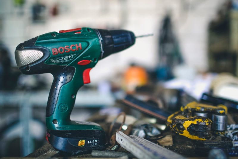 A Bosch 14.4V cordless power drill on a disorganised work bench.