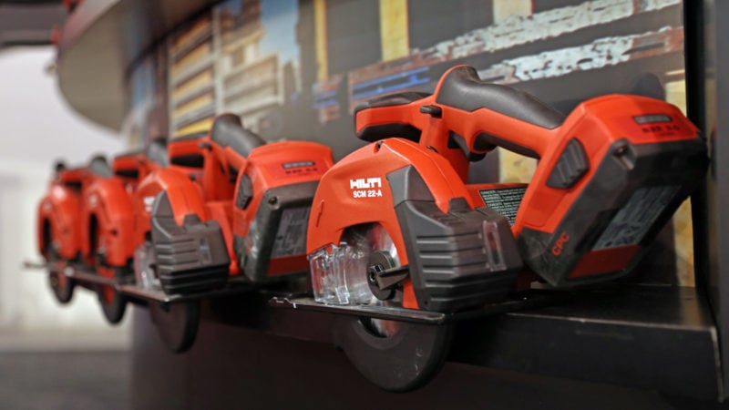 Four handheld cordless Hilti circular saws placed on a shelf.