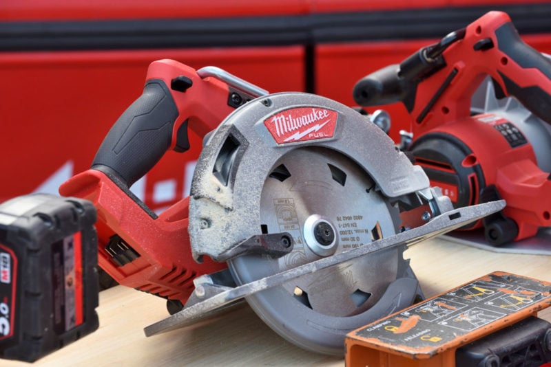 Several Milwaukee cordless saws on a wooden table.