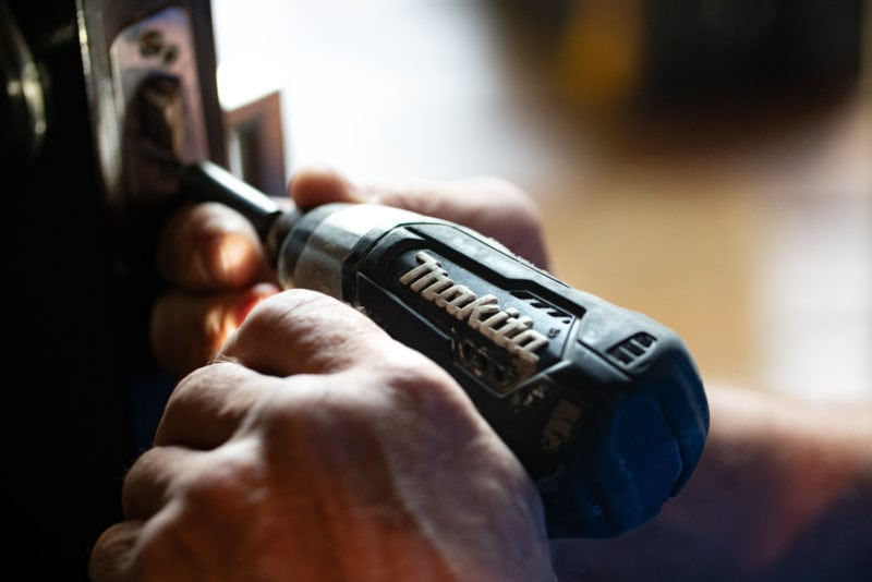 A person using a Makita power drill to secure a door locking mechanism in place on a door.