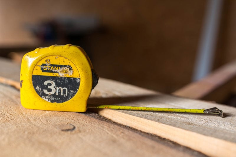 A yellow Stanley 3 meter long tape measure on a wooden plank.