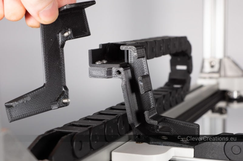 A black 3D printed drag chain bridge with its cover removed connected to a 10*15mm drag chain