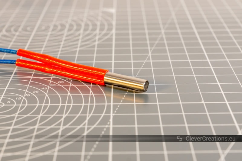 A metal 12V 40W hot end heater cartridge with red insulation placed on top of a grey cutting mat.