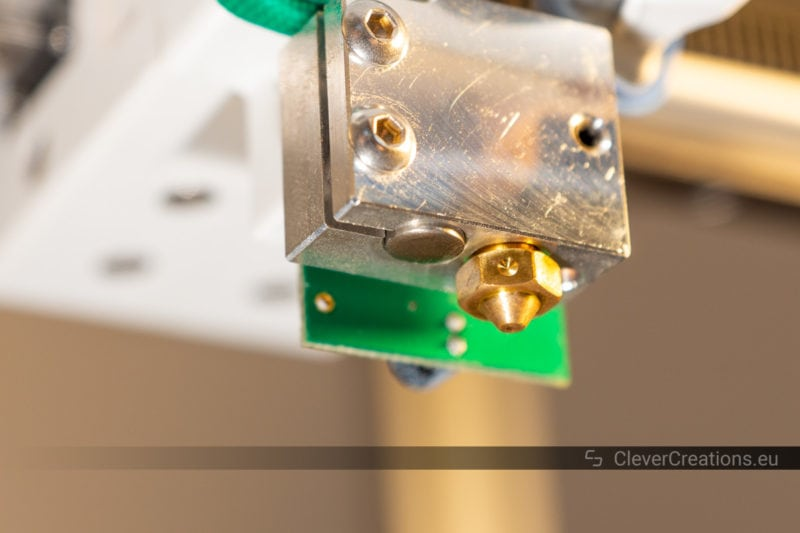 A close-up of a 3D printer hot end with the heater cartridge and nozzle visible at the underside.
