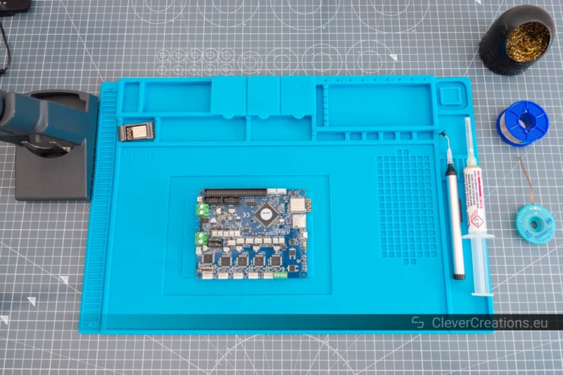 Top view of a blue silicone soldering mat with a circuit board on top and a variety of soldering tools spread around it.