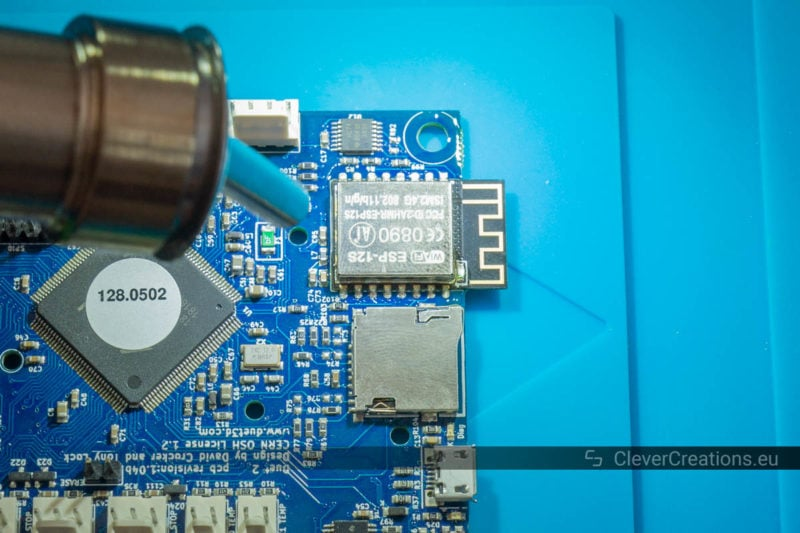 A hot air rework station nozzle melting the solder on a defective ESP8266 wireless module.