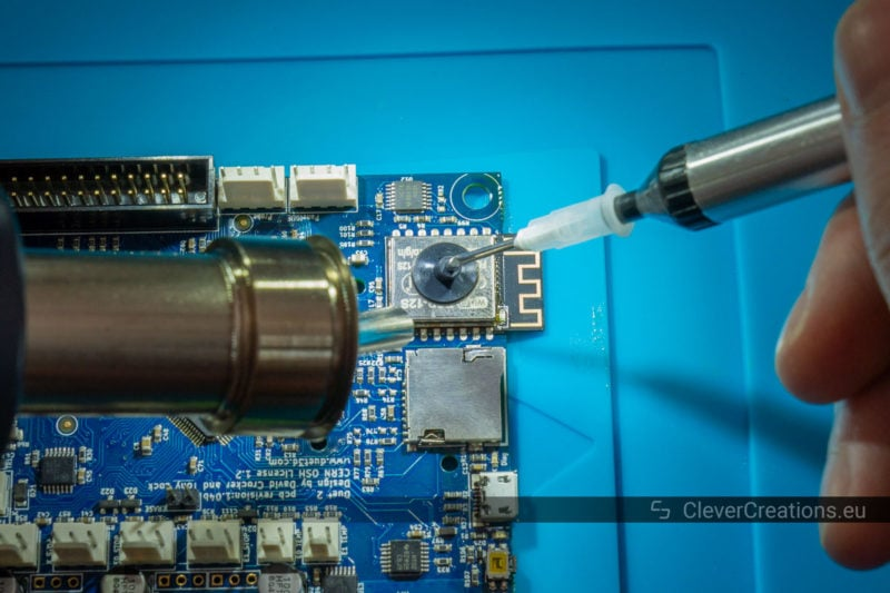 A hot air rework station nozzle blowing hot air on a PCB with a vacuum pickup tool being held on a broken ESP-12S module.