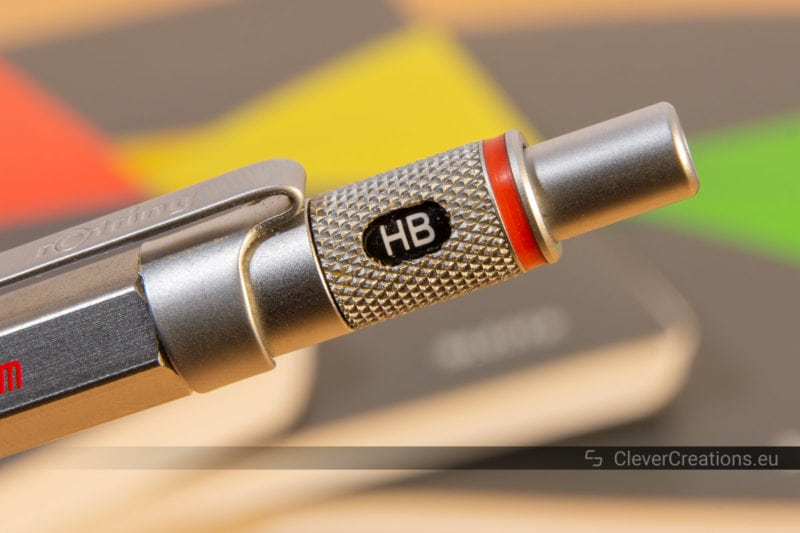 Close-up of a rotating lead hardness indicator on a metal mechanical pencil with several out of focus notebooks in the background.