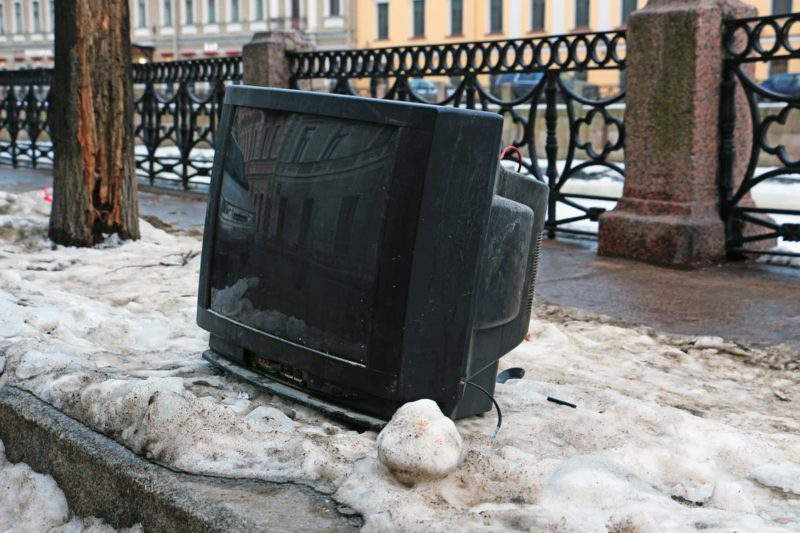 A discarded TV on a curb by the side of the road.