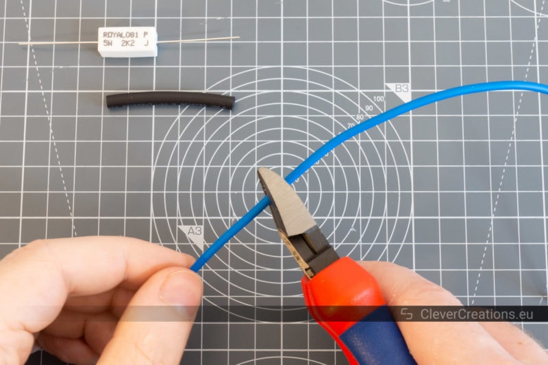 A pair of wire clippers being used to cut a blue wire.