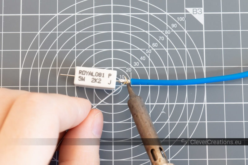 A soldering iron soldering a strand of wire to the lead of a 5W resistor.